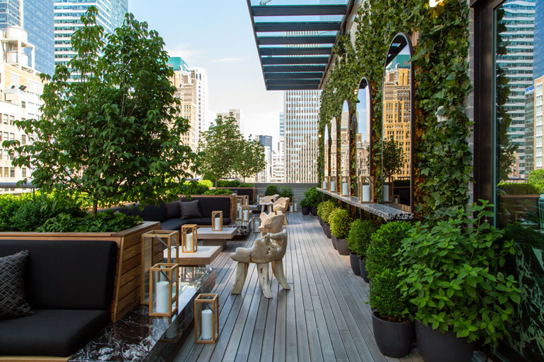 Ivy covers a wall in the outdoor area while mirrored arches reflect the city
