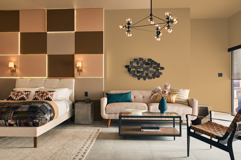 The warm Cellini Gold HDC-CL-18 shade pairs well with an accent wall and colorful decor. Photography courtesy of Behr Paint.