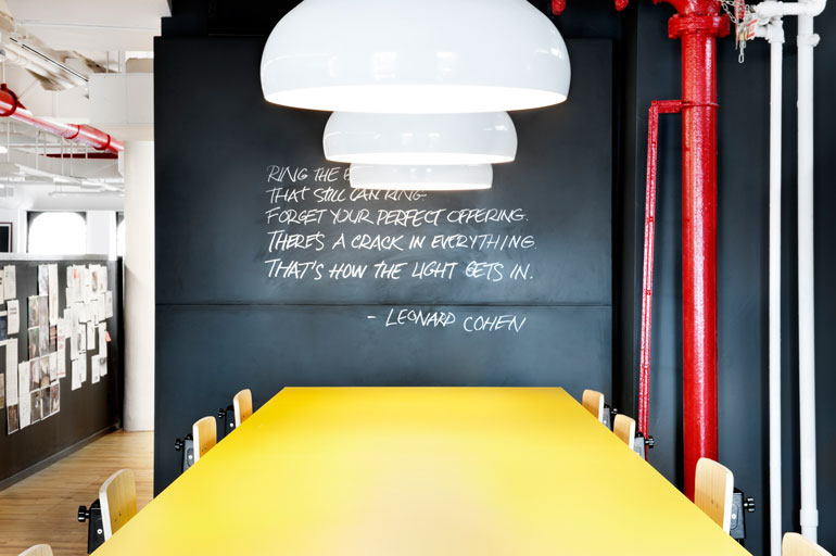 In A Communal Space, A Counter Height Table Is Topped In Yellow Laminate.  Photography By Emily Andrews.